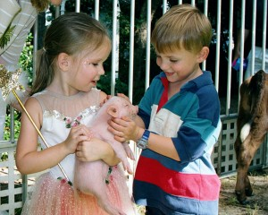 girl and boy with piglet